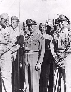 A crowd of men in uniforms. One at the left is wearing medals; one at the right is carrying a walking stick