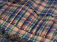 A kilt in the process of construction. The pleats are laid out and pinned in the style known as pleating to the sett in which the pattern of the sett will be repeated across the back of the kilt.