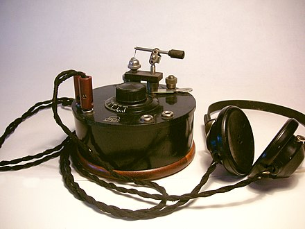 Swedish crystal radio from 1922 made by Radiola, with earphones. The device at top is the radio's cat's whisker detector. A second pair of earphone jacks is provided. Kristallradio.JPG