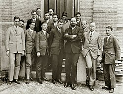 Fifteen men in suits, and one womyn, pose for a group photograph