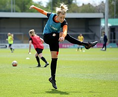 A female soccer player, who is mid air jump after kicking a powerful kick.
