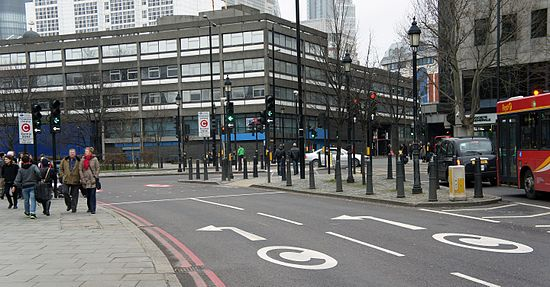 Street markings and signs with the white-on-red C alert drivers entering the congestion charge zone (CCZ) at Tower Hill.