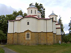 Back view of a white monastery church with an apse featuring a sharp-pointed window bay and four domes visible