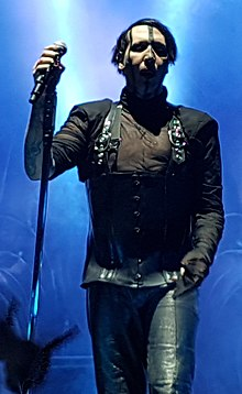 Image of the band's vocalist wearing black clothes and holding a microphone in his right hand. The background of the image is illuminated with blue stage lighting, and on the bottom left corner the hand of a concert-goer can be seen giving the 'devil-horns' signal.