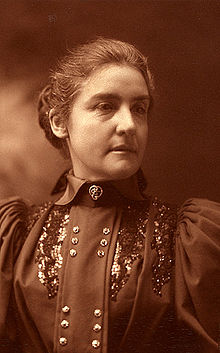 A black and white photograph featuring a woman wearing an old-fashioned dress and with hair drawn back into a bun.