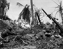 Un gruppo di soldati che strisciano attraverso una giungla in fiamme, con un bunker nascosto davanti a loro