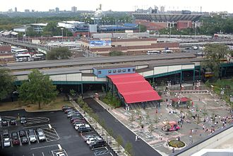 Mets–Willets Point (IRT Flushing Line) - The entrance/exit stairs for Mets-Willets Point station viewed from Citi Field. The Long Island Rail Road station is at rear left and the USTA National Tennis Center is at rear right.