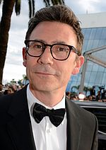 A picture of a man wearing black framed glasses and a tuxedo.