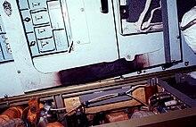 Bílý panel pokrytý tlačítky, který na spodní hraně vykazuje známky poškození ohněm.  Kabely a další kusy hardwaru jsou umístěny pod panelem.
