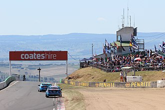 Mount Panorama Circuit - Cars on the run from McPhillamy Park to Brock's Skyline during the 2014 Bathurst 1000, with spectators areas at McPhillamy Park on the right.