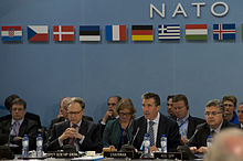 An older man in a suit sits, speaking at a round table with dozens of other men and women. Above them is the word NATO and nine European flags.
