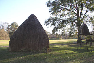 Natchez people - Platform mounds (in the distance) and reconstructed wattle-and-daub house at the Grand Village of the Natchez.