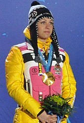 A woman, wearing a predominately yellow and pink jacket and a black cap, stands in front of a blue background, looking to the right. She hold flowers in her hands and has a gold medal around her neck.