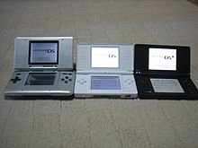 Three opened clamshell dual-screen handheld devices sit next to each other.