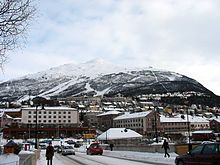 View of a town with buildings and streets covered with snow. In the background, behind the town, there are high, snowy mountains.