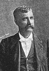 A man in his forties with black hair and a long mustache wearing a white shirt and black coat, facing right