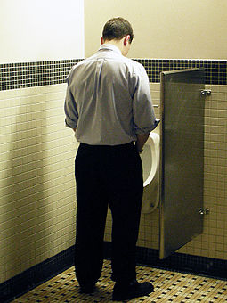 A man uses a urinal while urinating in a standing position. Peeing .jpg
