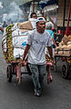 Person carrying utensils for sale on a cart.jpg