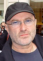 A picture of a man with glasses. He wears a black cap and a black coat over a dark blue shirt.