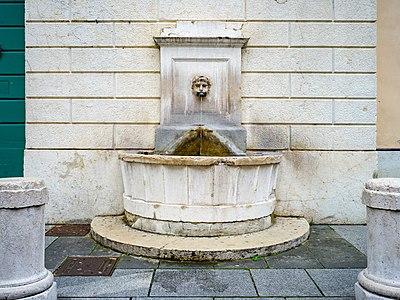 Fountain and mascarone of satyr on Piazza Arturo Benedetti Michelangeli square in Brescia