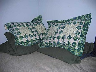 Pillow - Decorated pillows piled on the corner of a bed
