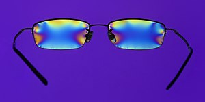 English: Stress in a pair of plastic glasses m...