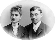 A charming and iconic period photo of a young couple around 1900. The lady has her hair swept upwards and is wearing a high collar fastened with a jewel. The gentleman sports a gallant moustache neatly trimmed and is also wearing a high collar.