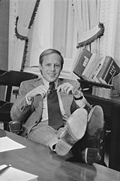 Casual portrait of John Dean sitting in his office with his feet on the desk