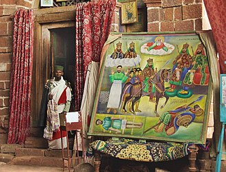 Na'akueto La'ab - Priest with Large Canvas at the Church of the Monastery of Na'akueto La'ab, with a depiction of the legend of kings