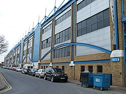 An external view of a sports stadium, with a large amount of blue detail on the facade.