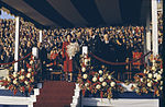 Princess Elizabeth holding flowers on stage with Prince Philip and several people. Royal Visit 1951, Ontario.jpg