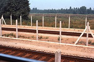 Deutsche Bundesbahn - West German trains ran through East Germany. This 1977 view shows how barriers were made near the tracks to keep people away.