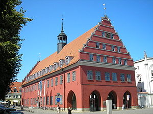 University of Greifswald - Greifswald's red town hall, the seat of the Lord Mayor, is situated in the historic city centre. As Greifswald is a small, coastal student town, the relationship between the university and the town has mostly been close. For instance, it was Heinrich Rubenow, then Lord Mayor of the city, who pushed for the establishment of a university in his town, and who became the university's first rector in the year 1456.