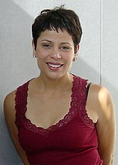 A woman with short brown hair and a red top is smiling toward the camera.