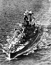 Aerial photograph of Royal Oak under way at sea, flying both the Norwegian flag and the White Ensign at half-mast.