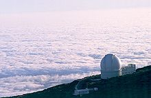 Aerial view of white domed building on side of mountain with floor of white clouds extending to the horizon below and behind the mountain.