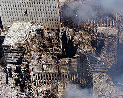 Portions of the outer shell of the North Tower lean against the remains of 6 WTC which suffered massive damage when the North Tower collapsed. The remains of 7 WTC are at upper right