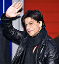 Dark-haired man dressed in black, waving