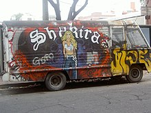 "A portrait of a woman dressed in a white crop top and blue pants is painted on a colourful van. The word ""Shakira"" is written in white behind her."