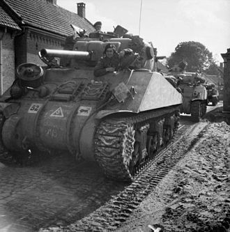 "11th Armoured Division (United Kingdom) - M4 Shermans of the 23rd Hussars advance through Deurne, 26 September 1944. Note the ""Charging Bull"" on the first tank's front hull (third marking from the left), the division's emblem."