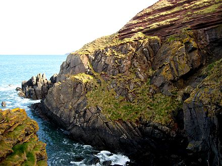 Cliff at the east of Siccar Point in Berwickshire, showing the near-horizontal red sandstone layers above vertically tilted greywacke rocks.