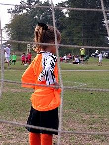 vue de derrière les filets d'une jeune gardienne de but de dos habillée en maillot orange et short noir.