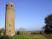 Circular brick tower. Steps and a metal railing are visible at the top.