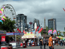 Crowds of people wander around booths selling carnival food. A merry-go-round is in the foreground to the left, and several skyscrapers stand in the background.