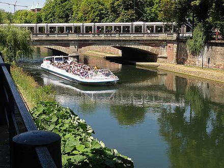 One of Strasbourg's trams passes over one of its canals, whilst a tourist trip boat passes underneath Strasbourg PontTheatre 02.JPG