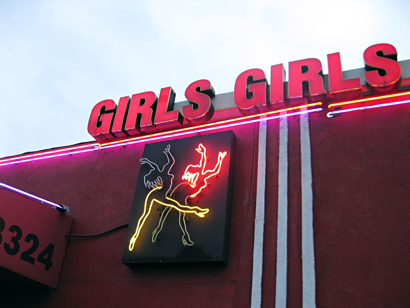 "Photo of the exterior of a strip club with a neon sign that says, ""GIRLS GIRLS."""