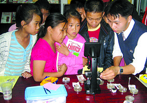 "Science education - Young students use a microscope for the first time, as they examine bacteria a ""Discovery Day"" organized by Big Brother Mouse, a literacy and education project in Laos."