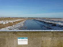 Tidal river between snowy banks, seen from an overbridge with a helpful notice