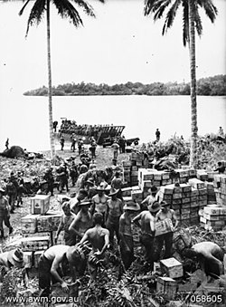 Crates of stores being unloaded from landing craft by soldiers and stacked on the shore