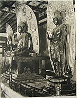 Three-quarter view of a central cross-legged seated statue on a pedestal flanked by two standing statues of almost the same size. The central figure has the palm of his right hand facing forward and that of the left hand upwards with the left hand resting on his knee. The flanking statues show a similar pose with their right hand while their left arm is hanging down. All three statues have halos in their back which are decorated with small cross-legged seated statues.